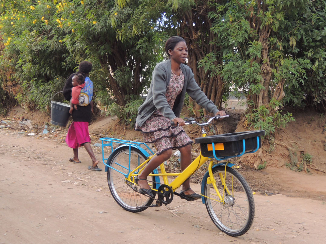 Beehive Enterprises worker Selina Masamba riding a refurbished Royal Mail bike.