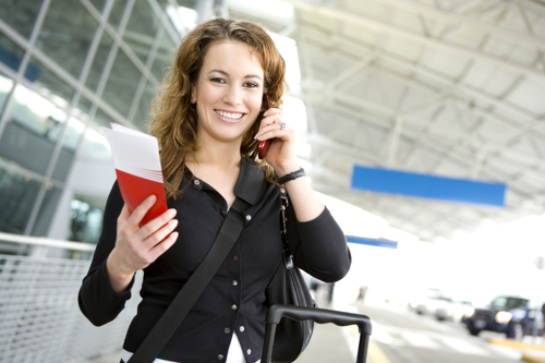 Traveler using her cell phone at an airport